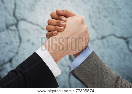 business, people and competition concept - close up of two people hands arm wrestling over concrete wall background