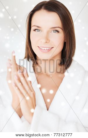 beauty, spa and people concept - beautiful woman standing in bath robe over snowy background