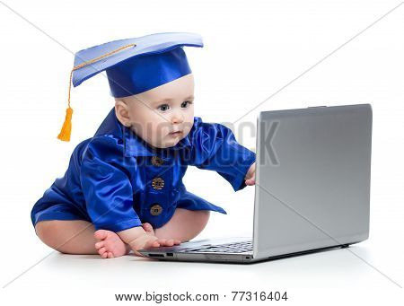 baby in academic dress works on laptop