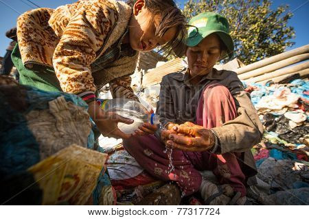 KATHMANDU, NEPAL - DEC 24, 2013: Unidentified child and his parents during lunch in break between working on dump. Only 35% of population Nepal have access to adequate sanitation.