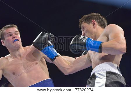 NOVOSIBIRSK, RUSSIA - NOVEMBER 29, 2014: Match Boris Georgiev (right) of Bulgaria vs Viacheslav Kislitsyn of Ukraine during AIBA Pro Boxing tournament. The winners will go to the Olympics-2016