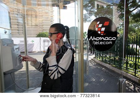 MONTE CARLO, MONACO - OCTOBER 29, 2014: A young woman uses an outdoor pay telephone owned and operated by state telecommunications carrier Monaco Telecom International (MTI)