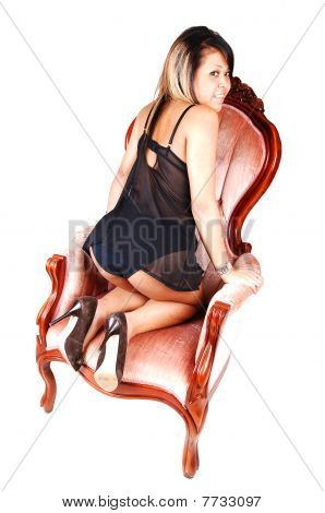Asian Girl Kneeling In Armchair.