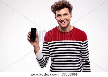 Happy man showing a blank smartphone display
