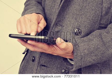 a businessman wearing a coat using a tablet, with a filter effect