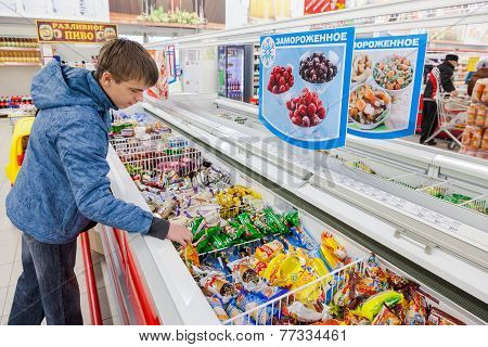 Young Boy Choosing Ice Cream At Shopping In Supermarket
