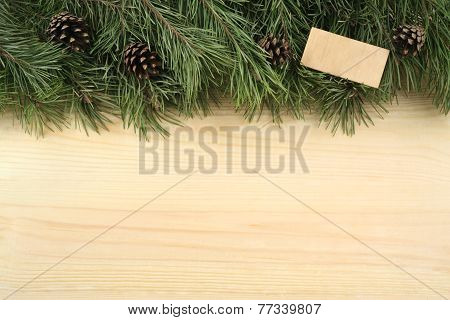 Christmas fir branches, bumps and wooden plate on a wooden background.
