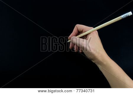 Hand Holding Wooden Pencil Isolated On Black Background
