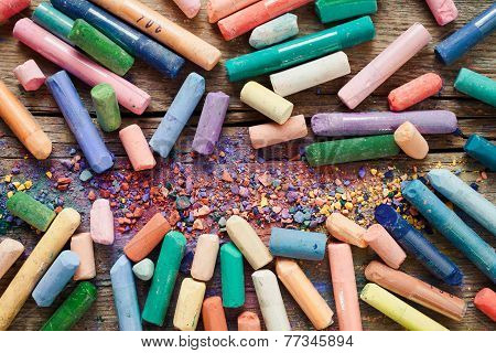 Collection Of Rainbow Colored Pastel Crayons With Pigment Dust On Old Desk.