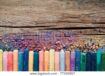 Pastel Crayons And Pigment Dust On Rustic Wooden Background.