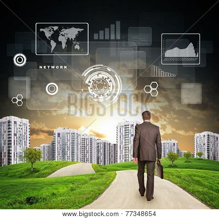 Businessman walking along road running through grassy hills towards city, at sunset. Chart, drafts,
