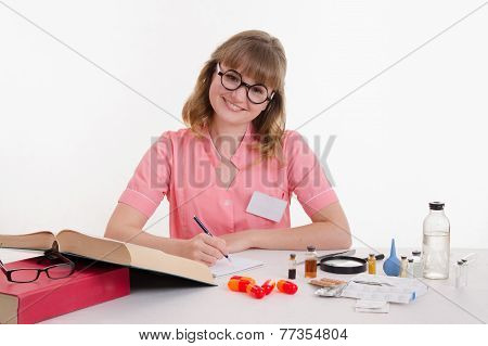 Pharmacist Writing In Notebook Sitting At A Table