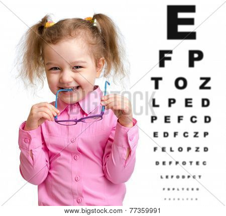 Smiling girl took off glasses with blurry eye chart behind her