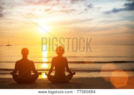 Young yoga couple meditating during amazing sunset on the ocean beach.