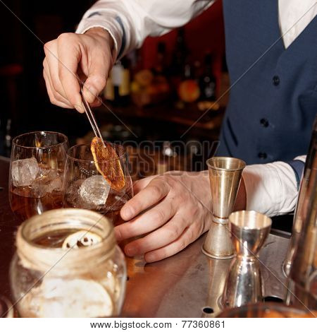 Barman works at bar counter, warm tone