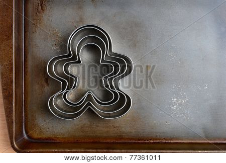 Overhead closeup of gingerbread men cookie cutters on a well used baking sheet. Horizontal format with copy space. Strong sidelight.