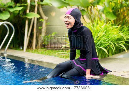 Muslim woman or girl sitting at pool in tropical garden wearing Burkini halal swimwear