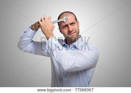 Man using a 19mm wrench to fix his brain