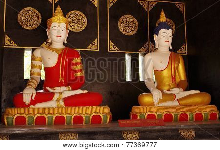 Buddha in red & Buddha in gold side by side.
