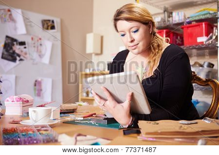 Jeweler Checking Orders For Business With Digital Tablet