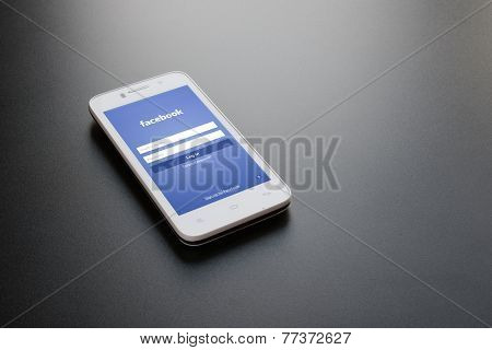 ZAPORIZHZHYA, UKRAINE - NOVEMBER 07, 2014: White Smart Phone with Facebook Social Network Log In Screen on the Black Table.