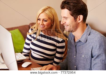 Couple Sitting At Computer In Home Office Shopping On Line