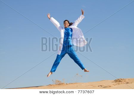 intern jumping on beach