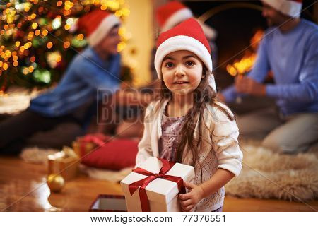 Little girl in Santa cap holding giftbox