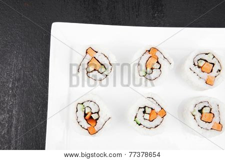 Maki Sushi - California Sushi Roll with Avocado, Cream Cheese and Raw Salmon inside. With wasabi . over black table