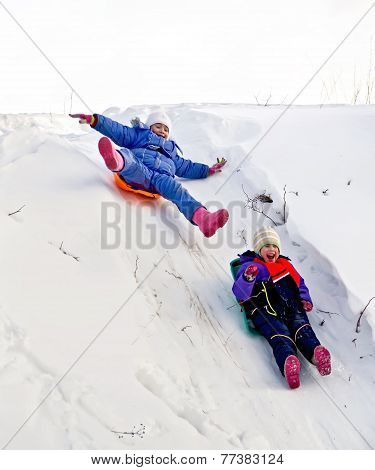Two Girls On Sled Through The Snow To Slide