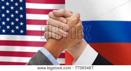 partnership, politics, gesture and people concept - close up of two hands armwrestling over american and russian flags background