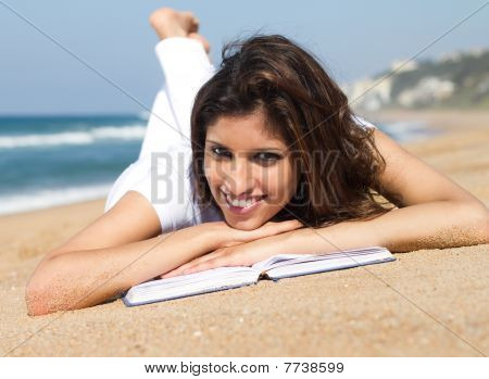 beautiful woman reading on beach
