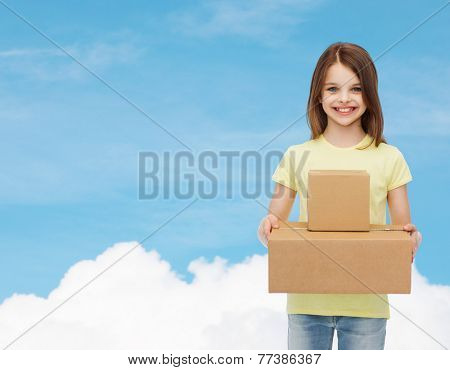 advertising, childhood, delivery, mail and people - smiling little girl holding cardboard boxes over blue background