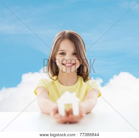 home, education, happiness, childhood and people concept - beautiful little girl sitting at table holding white house cutout over blue sky background