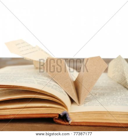 Origami airplanes on old book, on wooden table, on white background