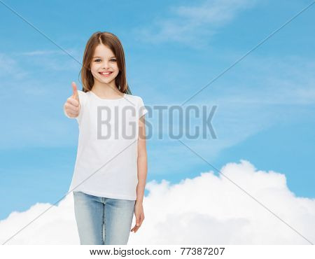 advertising, dream, childhood, gesture and people - smiling little girl in white blank t-shirt showing thumbs up over blue sky background