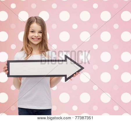 advertising, people, direction and childhood concept - smiling little girl with white blank arrow pointing right over pink white polka dots pattern background
