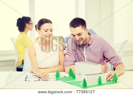 startup, education, architecture and office concept - smiling architects with house model and blueprint working in office