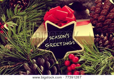 a star-shaped signboard with the text seasons greetings written in it, with a gift and some natural ornaments such pine cones and red berries in the background
