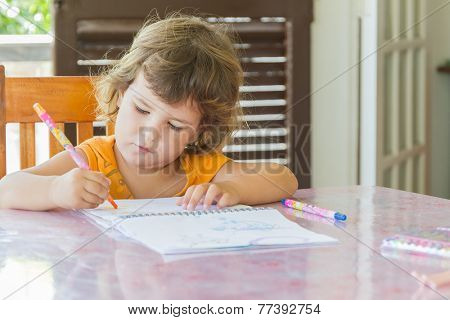 indoor portrait of cute child girl drawing at home