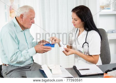Doctor shows the patient how to use daily dose pills