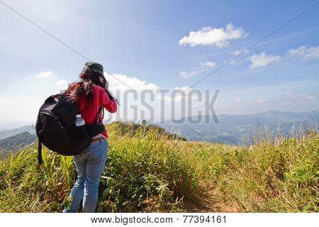 Hiking Tourist Taking Photos Of The Alpine Landscape