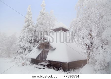 Forest hut covered with snow.
