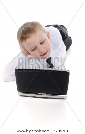 Little Boy Lying On The Floor With A Laptop.