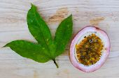 picture of passion fruit  - Ripe passion fruits and leaf on wooden background - JPG