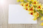 stock photo of gladiolus  - bouquet of beautiful yellow gladioluses and a blank sheet of paper for inscription on the wooden background - JPG