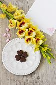 pic of gladiolus  - chocolate heart on a plate yellow gladioluses and a blank sheet of paper for inscription on the wooden background - JPG