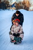 stock photo of toboggan  - young smiling  people fun sledding outdoors in winter day - JPG