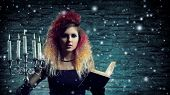 stock photo of witchcraft  - Beautiful witch making witchcraft over winter background - JPG