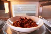 foto of oven  - Leftover Chili Cooking Inside Microwave Oven - JPG